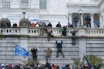 Protestujúci lezú po budove Kapitolu.