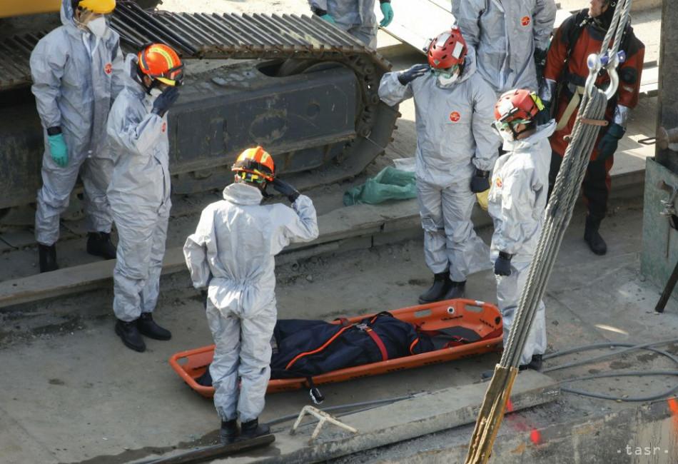 Na snímke kórejskí členovia záchranárskeho tímu vzdávajú poctu jednej z obetí, ktorá zostala uväznená v potopenom vraku výletnej lode Hableány po vytiahnutí pri Margitinom moste na rieke Dunaj v Budapešti 11. júna 2019. Foto: TASR/AP